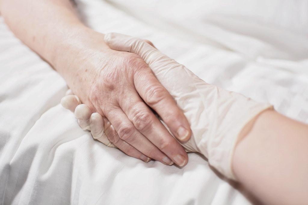 Deux mains qui se tiennent un soignant et une personne malade