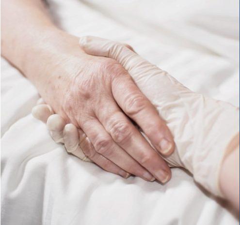 Main de soignant tenant la main d'un patient